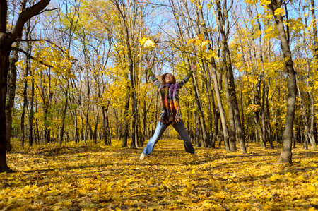Woman jumping amongst autumn leaves photo