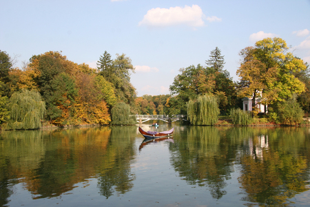 arbour: Beautiful autumn park. Arbour seen through autumn leaves. Boats floating on the river. The water reflects the autumn forest Stock Photo
