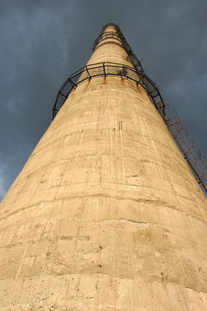stormy sky: Factory chimney with ladder on a background of a stormy sky. Bottom view. Stock Photo