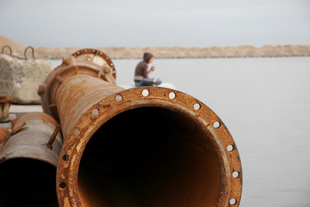 An old rusty pipe on the lake. Stock Photo