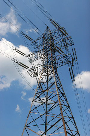 end user: Electric transmission line tower with wires and transformer against the bright sky