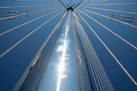 shallop: The mast of the yacht looking to the blue sky. Metal ropes, tackle