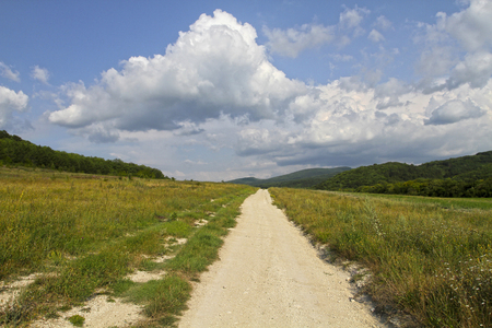 unpaved road: Unpaved dirt road takes to the sky with clouds