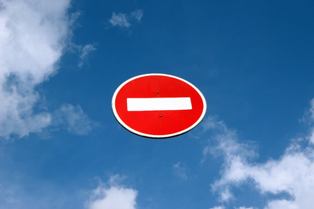 atheism: Directions closed road sign against the blue sky. White brick rectangle in the red circle