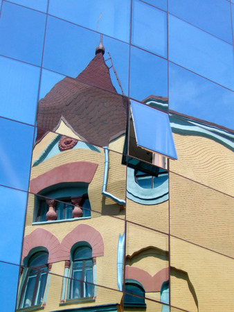 transom: The old in the new. Reflection of an old house in a beautiful large blue windows of a new high-rise building Stock Photo