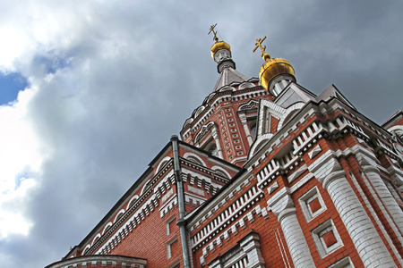 love dome: Christian Orthodox Cathedral of red and white brick with two gilt domes and crosses. Photographed in an unusual perspective from below