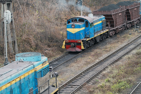 diesel locomotives: Railway junction with a freight train. The locomotive carries cars with coal