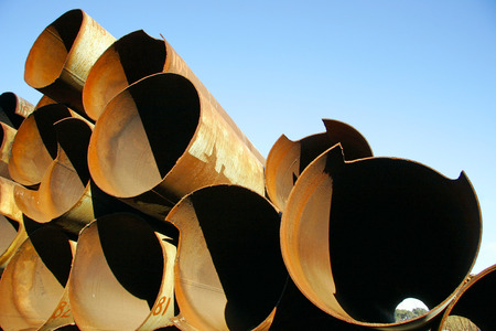 Rusty iron pipes of large diameter lie on each other