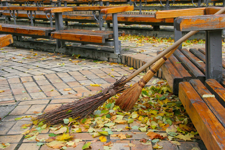 Broom and the broom standing near the bench area in the autumn. Cleaning street from the park autumn leaves.
