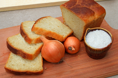 Homemade bread baked at home with their own hands, lying on a wooden board cut. Two onions lie next to the salt and homemade white bread. Stock Photo