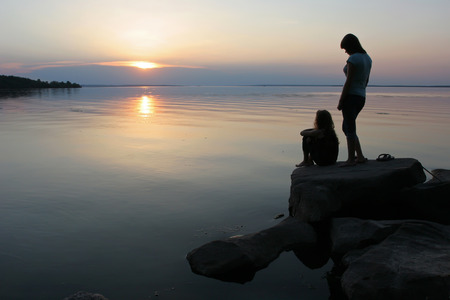 Two girls watching the sunset from the water