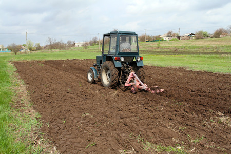 agri: Tractor with plow fastened spring plowed field. Spring care of the farmer, the opening of the season of spring agricultural works.