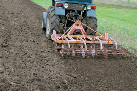 Tractor with cultivator harrow the ground fastened. Summer season opens plowing and cultivating the garden.