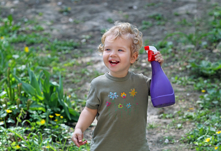 White kid with a spray helps parents take care of flowers and plants. Emotional boy is playing with water Stock Photo