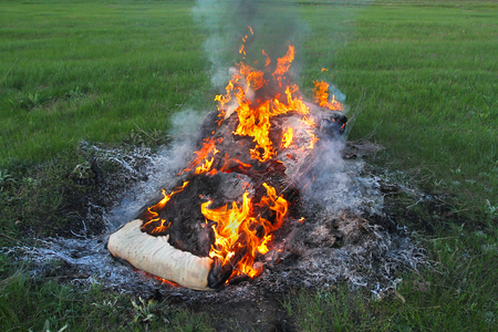 On a green field in the fire burned the old spring mattress. Fire destroys the past. Stock Photo
