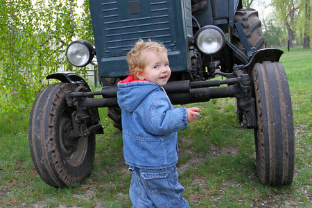 Little boy jeans standing in front of the old blue tractor.