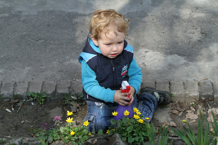 White kid with a spray helps parents take care of the flowers and plants. Little boy sitting among the fallen petals of a blooming garden. Stock Photo