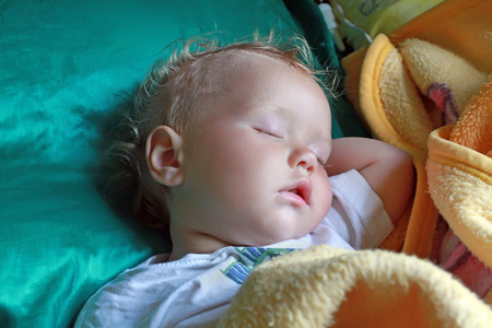 Small white curly baby sleeping sweetly placed a hand under head
