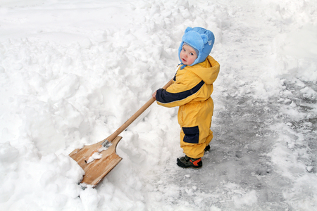Little boy with big wooden shovel to clear snow. A very snowy winter