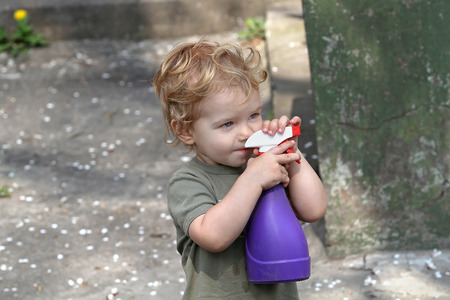 White kid with a spray helps parents take care of flowers and plants Stock Photo