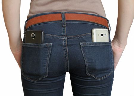 The girl Two different smartphone in the rear pocket of jeans. Two cameras to shoot video. Isolated object on a white background.