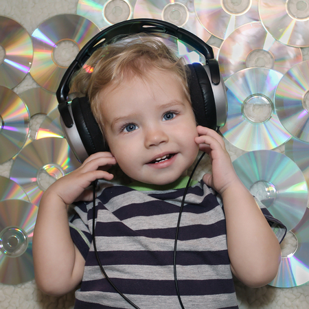 A little boy in headphones listens to music. White Boy in headphones lying on disks. Baby listening to a lullaby and is preparing to sleep