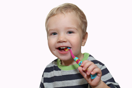 Baby with white first teeth brushing teeth with a toothbrush. White little boy with a toothbrush in his hand. Baby chewing on children's toothbrush prevention of dental diseases. Photo on a white background Stock Photo