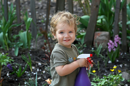 Very positive smiling white kid with dirty face helps parents watering flowers in the garden. Little boy with a spray gun on the background of the picturesque old fence and green plants Stock Photo