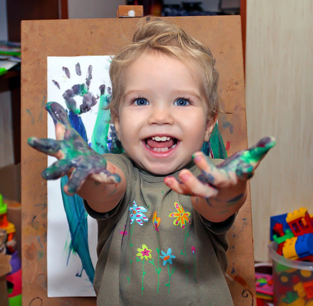 Small child with blue eyes, drawing finger paints. Babe shows palms soiled in a paint. Little painter with an easel painting the grass. Stock Photo