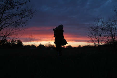 Silhouettes of a boy with a camera on the background of sunset