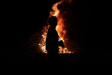 Silhouettes of a boy with a camera on the background of fire Stock Photo