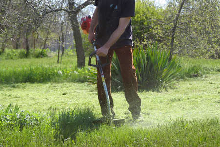 A man with a gas cutter mows the lawn