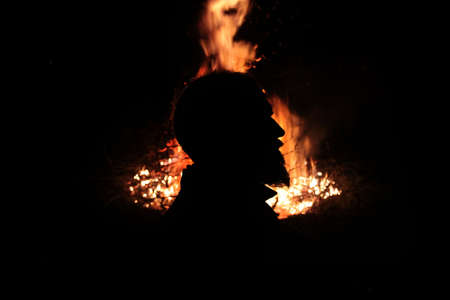 Profile of a man with a beard against the background of fire
