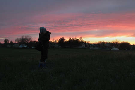 A boy with a camera taking pictures of the sunset Stock Photo