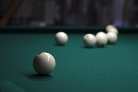 Billiard balls on a table in a dark room.