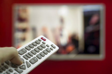 The remote in the hand switch channels on the TV hanging on the red wall.