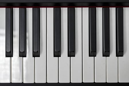 Simple and clean piano keys, one octave, music closeup, space for text on black background. Stock Photo