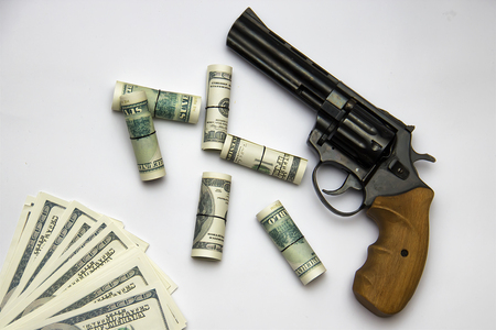 A huge revolver on a white background with hundred-dollar bills. Stock Photo