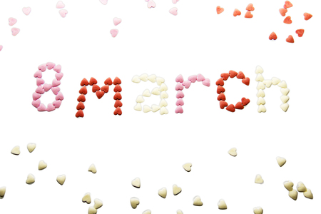 March 8, the world womens day, is written on a white background with small sugar hearts. Isolate Stock Photo