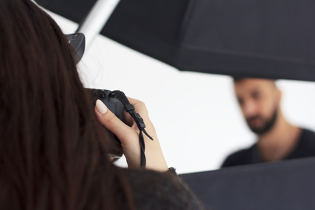 Photographing in the studio, a photographer and a model enjoy filming.