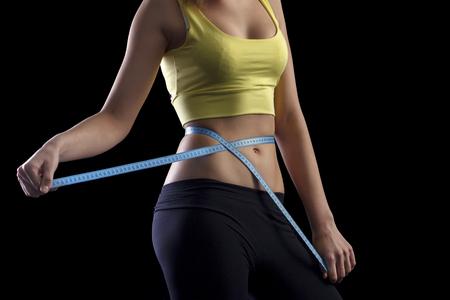 Happy fitness girl measuring her waistline over black background.