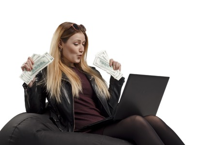 young woman earns crypto currency, girl sits on a soft chair with a laptop and dollars in hands, bitcoin.