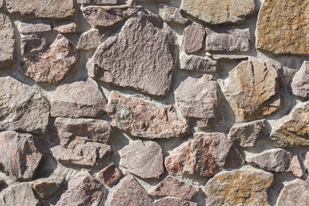 Wall made of granite stones as background.