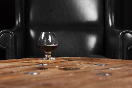 a glass for cognac on a wooden table on the background of a leather chair