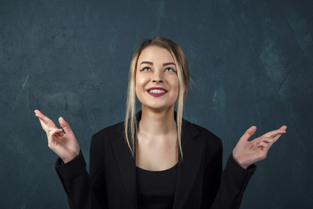 Portrait of a beautiful woman in a black suit close-up, the girl crosses her fingers and smiles against a blue textured wall with space for text. Stockfoto