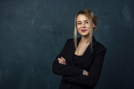 Close-up portrait with lots of details, beautiful smiling woman in black suit against a blue textural wall background with place for text. Stockfoto