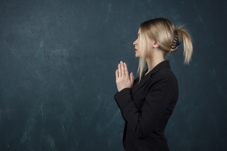 Portrait in a profile of a beautiful woman folded in front of her hands in a black suit against a blue textured wall with space for text