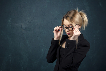 Young successful office working woman adjusting glasses.