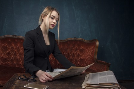 Portrait of a beautiful woman in a black suit reading a newspaper in an expensive antique interior against a blue textured wall with space for text. Business lady, a successful independent young girl. Stockfoto