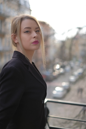 Portrait of a young woman in a black suit close-up against a background of a blurry city in the rays of the setting sun. Stockfoto